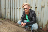 Young bearded man crouching outdoor — Stok fotoğraf