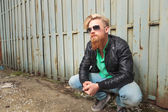 Crouched young bearded man  — Stock Photo