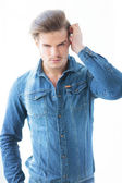 Man in jeans clothes arranging his hair — Stock Photo