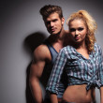 Young muscular man looking away near girlfriend — Stock Photo