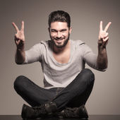 Seated young man making the victory hand sign — Stock Photo