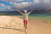 Man walking on the beach and celebrates his joyous life — Stockfoto
