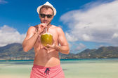 Man drinks juice from a coc nut on a beach — Stock Photo