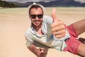 Man lying  on beach  and makes the ok  sign — Stock Photo