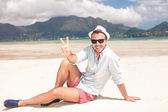 Man making the victory peace sign  on the beach — Stock Photo