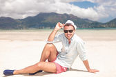 Man sits on the beach and holds his hat — Stock Photo