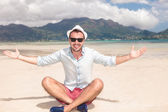 Seated happy young man invites you to the beach — Stock Photo