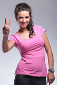 Casual woman making the victory peace sign — 图库照片