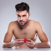 Naked young man holding a red ball  — Stock Photo