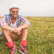 Smiling young casual man sitting in a field — Stock Photo