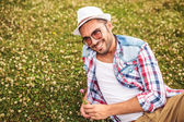 Casual man picking a flower from a field and smiles — Stock Photo