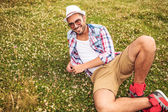 man with hat  laying down on  field and smiles — Stock Photo