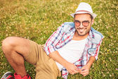 Casual man laying down on a grass field — Stock Photo