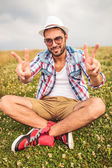 Man sits on a field  and makes the victory sign — Stock Photo