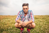 Serious crouched casual man in a field of grass — Stock Photo