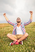 Seated man celebrates success with hand in the air — Stock Photo