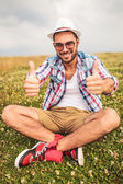 Man sits on a field and makes the ok sign — Stock Photo
