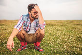 Crouched casual man in a grass field thinking  — Stock Photo