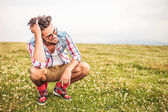 Laughing crouched man passing his hand through his hair — Stock Photo