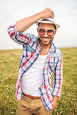 Happy young casual man holding his hat and smiles — Stock Photo