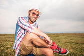 Relaxed casual man sitting on a chair in a field  — Stock Photo