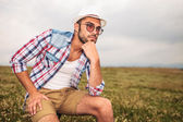 Pensive young casual man sitting on a chair outdoor — Stock Photo