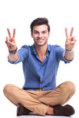 Seated casual man making the victory sign and smiles  — Stock Photo