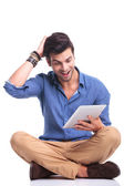 Amazed seated casual man reading good news on  tablet — Photo