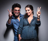 Young happy couple making the victory  sign — Stock Photo