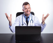 Young happy doctor at his desk welcoming you — Stock Photo