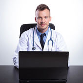 Young doctor sitting at his desk  — Stock Photo