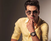 Attractive man with sunglasses holding his chin — Stock Photo