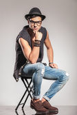 Serious fashion man sitting on chair is thinking — Stockfoto