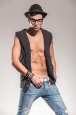Sexy fashion model holding his belt — Stock Photo