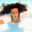 Woman wearing a white shirt swimming underwater — Stock Photo