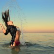 Girl splashing the sea water with her hair — Stock Photo #12313538