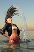 Chica salpicando el agua de mar con su cabello — Foto de Stock