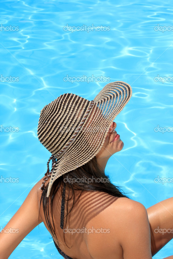 Young woman with hat enjoying a swimming pool  Stock Photo #12315731