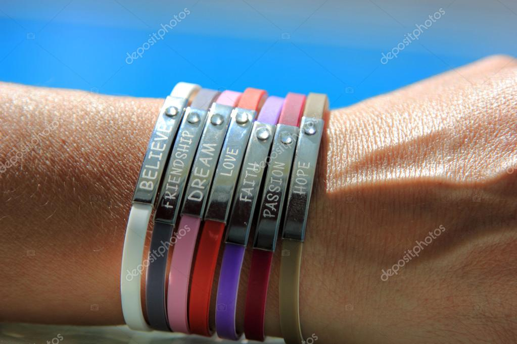 Woman wrist with bracelets with the words faith, believe, friendship, dream,hope,passion,and love — Stock Photo #12316375