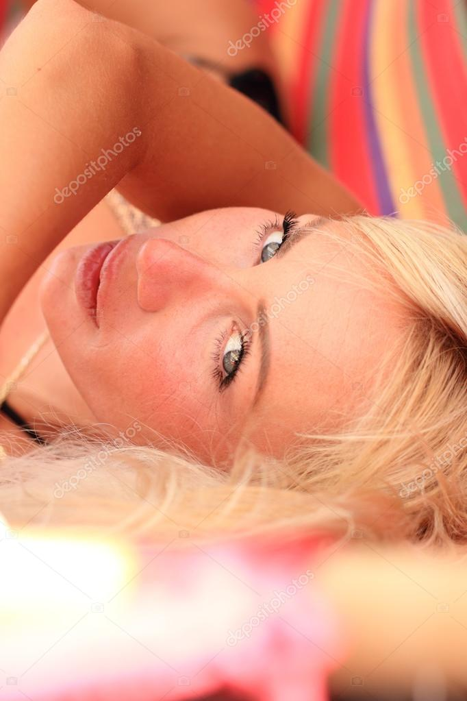 Woman sunbathing in bikini at tropical travel resort. Beautiful young woman lying on sun lounger  Stock Photo #12316528