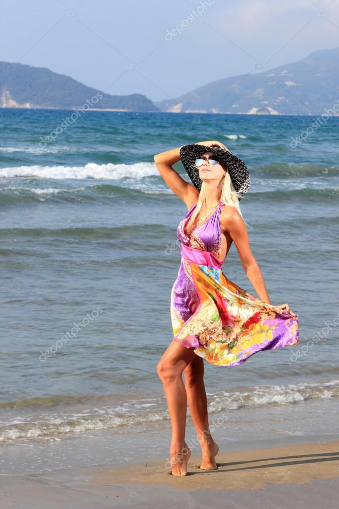 Young woman in dress and straw hat walking on beach — Stock Photo #12316997