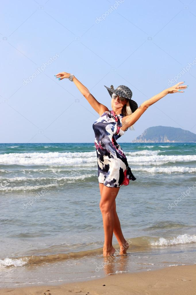 Young woman in dress and straw hat walking on beach  Stock Photo #12317084