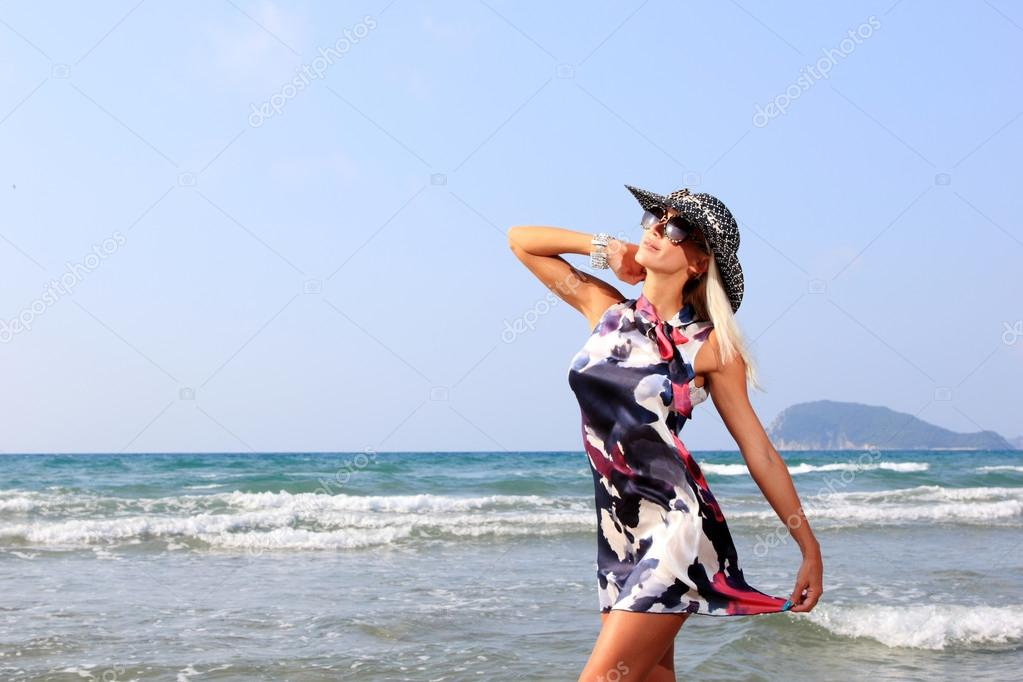 Young woman in dress and straw hat walking on beach — Stock Photo #12317090