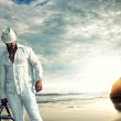 Travelling man holding a bag on the beach — Stock Photo #13511604