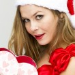 Stockfoto: Young woman in Santa hat holding gift box