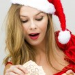 Foto de Stock  : Young woman in Santa hat holding piggy bank
