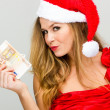 Stockfoto: Young woman in Santa hat holding piggy bank