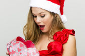 Young woman in Santa hat holding gift box — Stock Photo
