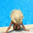 Woman sitting on the ledge of the pool. - Stock Photo