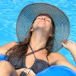 Woman in bikini and hat is in the water - Stock Photo